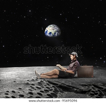 "Young man sitting on the Moon and reading a book with Earth in the background ""Elements of this image furnished by NASA"""