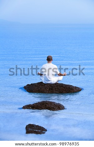 young man sitting on the rock in the water meditating