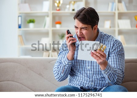 Young man sitting on the sofa with pills and prescription  #1175296741