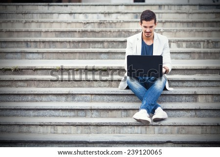 Young man sitting on the stairs using laptop #239120065