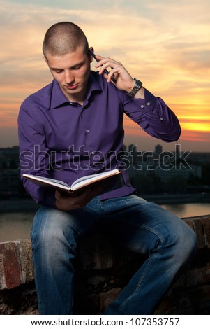 Young man sitting on the wall and makes a phone call