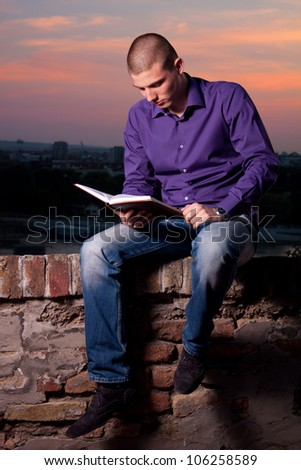 Young man sitting on the wall and reading a book