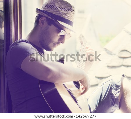 Young man sitting on the window playing the guitar