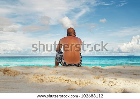 Young man sitting on tropical island beach sand in summer time with blue sky background
