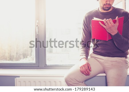 Young man sitting on window sill and reading a red book