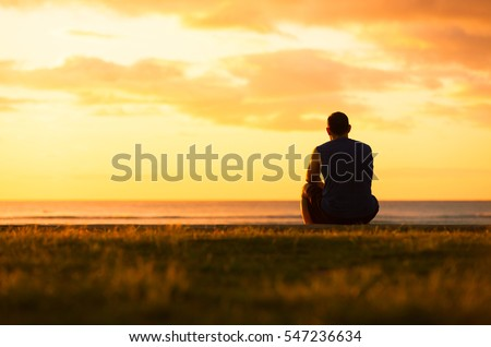 Shutterstock Young man sitting outdoors watching the sunset. Thinking and relaxing concept.