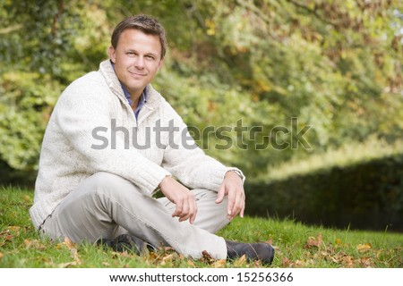 Young man sitting outside on grass in autumn landscape