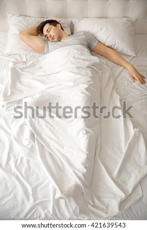 Young man sleeping alone in white big bed #421639543