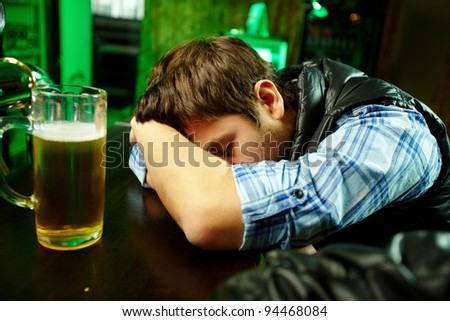 Young man sleeping in pub with glass of beer near by