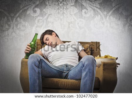Young man sleeping on an armchair while holding a beer bottle and a bowl of chips
