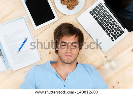 young man sleeping on the floor with laptop