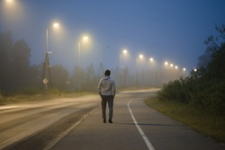 Young man slowly walking on long sidewalk under street lights in summer night. Spending time alone. Back view.