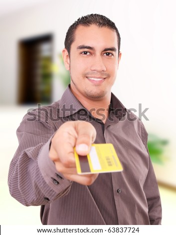 Young man smiling and giving his credit card