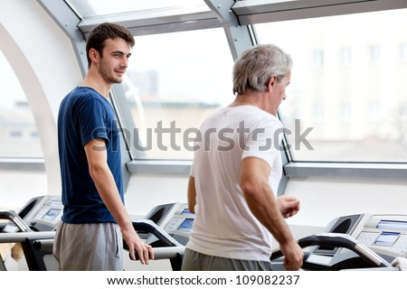 young man smiling and his father training in the gym: treadmill
