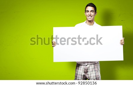 young man smiling and showing a big banner against a green background