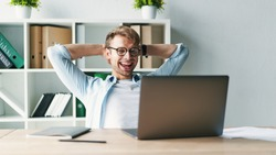 Young man smiling as he reads the screen of a laptop computer while relaxing working on a comfortable place by the wooden table at home. Happy Social distancing