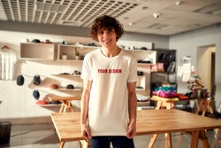 Young man smiling at camera, while trying on printed t shirt, standing in the store. Clothes at custom T-shirt, clothing printing company. Horizontal shot. Selective focus