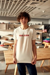 Young man smiling at camera, while trying on printed t shirt, standing in the store. Clothes at custom T-shirt, clothing printing company. Vertical shot. Selective focus