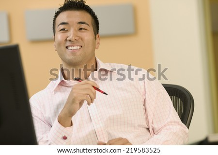 Young man smiling at his desk