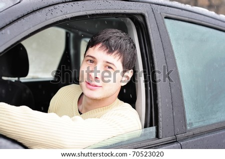 young man smiling, proud of his new car