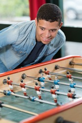 young man smiling while playing fussball