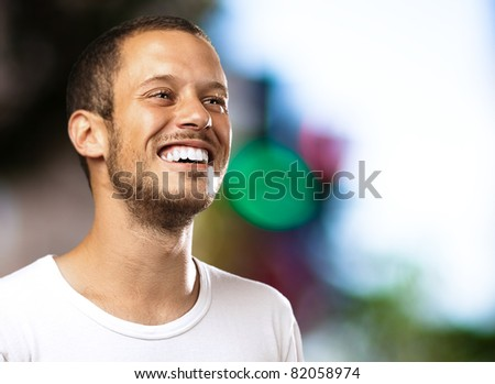 young man smiling with a city as a background