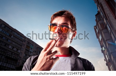 Young man smoking a cigarette on a city street