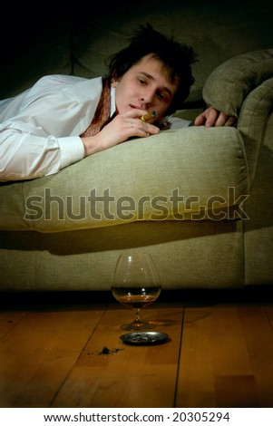young man smoking cigar and drinking cognac at night