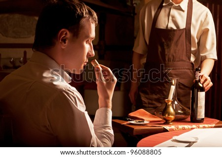 Young man sniffing the cork of a wine bottle