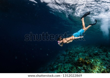 Young man snorkeling and skin diving over the coral reef edge in the tropical sea #1352022869