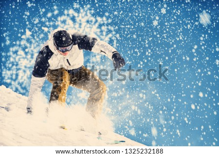 Young man snowboarder running down the slope in Alpine mountains. Winter sport and recreation, leisure outdoor activities. #1325232188