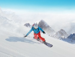 Young man snowboarder running downhill, Alpine mountains. Winter sport and recreation, leasure outdoor activities.