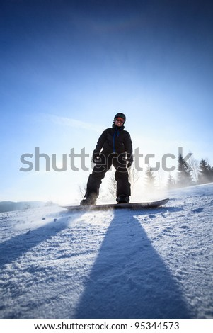 Young man snowboarding down a slope on a lovely sunny winter day