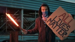 Young man solitary street protests stands with sign All Lives Matter on cardboard in hands background wall industrial building slow motion. Black Lives Matter protests in USA, Europe. Freedom concept
