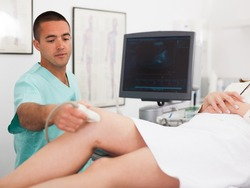 Young man sonographer using ultrasonography machine checking female patient in hospital diagnostic room