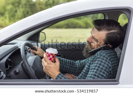 Young man speaking on phone and drinking coffee while driving his car #534119857