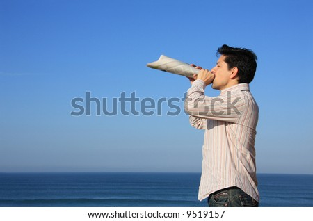Young man speaking with a newspaper megaphone