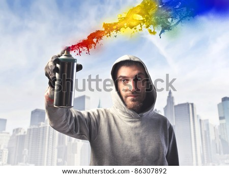 Young man spraying some colored paint with cityscape in the background
