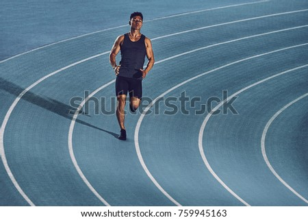 Young man sprinting on a blue indoor racetrack wearing sports clothing & looking tired after a training session. #759945163