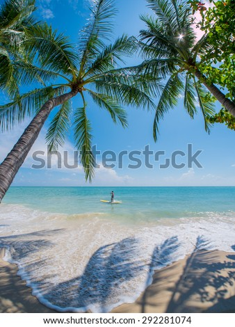 Young man stand up paddle surfing  in Thailand