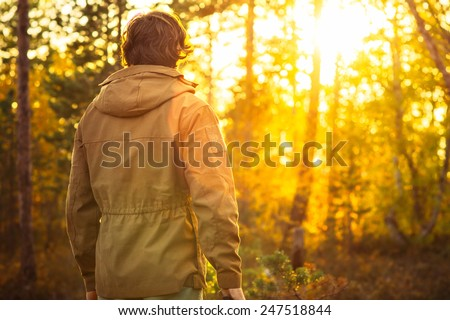 Young Man standing alone in forest outdoor with sunset nature on background Travel Lifestyle and survival concept