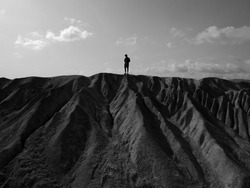 Young man standing alone on a steep cliff. Black and white photo.