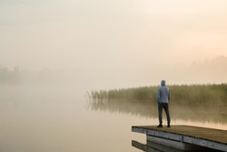 Young man standing alone on wooden footbridge and staring at lake. Mist over water. Foggy air. Early chilly morning. Empty place for sentimental, inspirational text, quote or sayings. Back view.