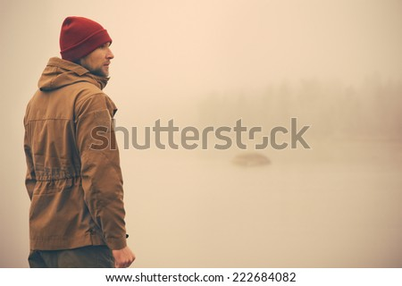 Young Man standing alone outdoor with foggy scandinavian nature on background Travel Lifestyle and melancholy emotions concept film effects colors