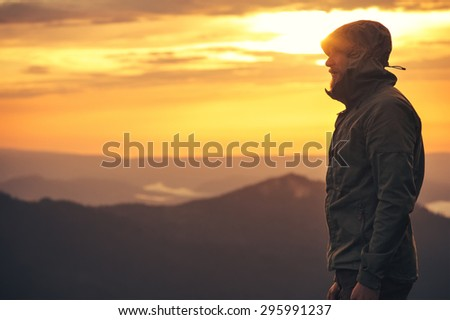 Young Man standing alone outdoor with sunset mountains on background Travel Lifestyle and survival concept