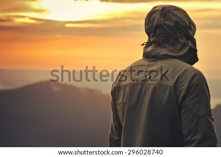 Young Man standing alone outdoor with sunset mountains on background Travel Lifestyle and survival concept rear view