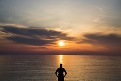 Young man standing at the beach in front of amazing sea view at sunset or sunrise and thinking about his future. Rear view