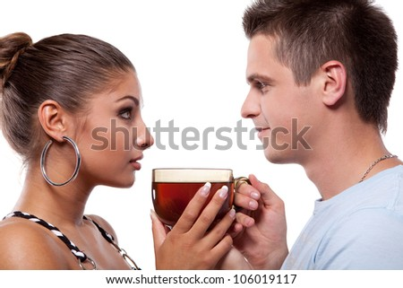 Young man standing beside beautiful woman and they holding a large cup of tea