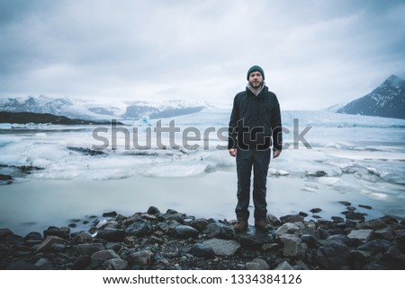 Young man standing in front of Fjallsarlon iceberg lagoon at the south end of the glacier Vatnajokull, with floating icebergs that calve from the edge of the glacier. Fjallsarlon iceberg lagoon at the #1334384126