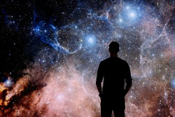 Young man standing in front of the huge picture of star nebula. Man in the universe. Man watching the space. Meaning of life. Visiting the observatory. Elements of the image furnished by NASA.